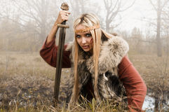 Viking girl with sword in a fog. Wood royalty free stock photos
