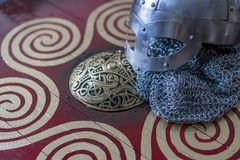 viking helmet with chain mail on a red shield with golden shapes Stock Photos