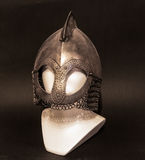 Viking helmet close-up. Steel knight helmet with hints of the sword impact on the black background Stock Images