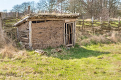 Viking henhouse. Part of viking age village replica in southern Sweden in early spring. Henhouse made of clay and juniper branches. Door closed, fence in Royalty Free Stock Photos