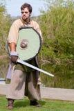 Viking-Krieger, der Klinge und Schild an der Anzeige hält Lizenzfreie Stockfotografie