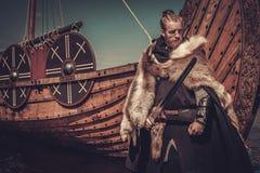 Viking-Krieger mit der Klinge, die nahe Drakkar auf der Küste steht Lizenzfreie Stockfotos