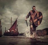 Viking krigare i attacken som kör längs kusten med Drakkar på bakgrunden Royaltyfri Foto