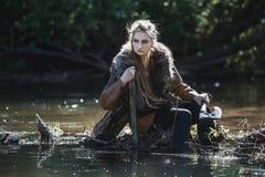 Viking kvinna med svärdet och hammaren som bär traditionell krigarekläder i en djup mystisk skog Royaltyfria Bilder