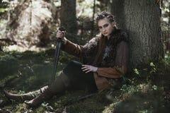 Viking kvinna med svärdet som bär traditionell krigarekläder i en djup mystisk skog royaltyfri foto