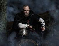 Viking med svärdet och hjälmen på en bakgrund av den rökiga skogen Arkivbilder