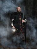 Viking med svärdet och hjälmen på en bakgrund av den rökiga skogen Fotografering för Bildbyråer