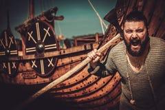 Viking med yxan som står nära drakkar på kusten arkivbild