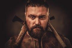 Viking med yxor i traditionell kläder för en krigare Royaltyfria Bilder
