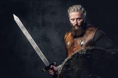 Viking rymmer den iklädda nordiska harnesken ett sköld- och silversvärd Arkivbild