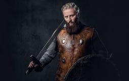 Viking rymmer den iklädda nordiska harnesken ett sköld- och silversvärd Arkivfoto