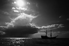 Viking ship and sun at sea. A silhouetted viking ship at sea (ocean) with the sun in the sky stock images