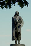 Viking Statue. A statue of famouse viking warrior Thorfinn Karlsefni, against a clear blue sky with tree leaves framing the top of the image Royalty Free Stock Photo