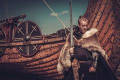 Viking-strijder met zwaard en schild die zich dichtbij Drakkar op de kust bevinden Stock Foto's
