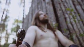 Viking-strijderszitting in het hout die tegen een boom leunen en een mes houden en de hemel met een ernstige blik bekijken moving stock footage