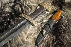 Viking sword and knife on a fur Stock Photos