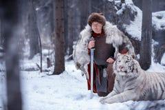 Viking-tribunes op één knie naast een witte tijger stock foto's