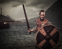 Viking warrior in the attack, standing along the shore with Drakkar and mountains on the background. Serious viking warrior in the attack, standing along the royalty free stock image