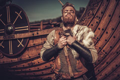 Viking warrior with axes standing near Drakkar on the seashore. Serious viking warrior with axes standing near Drakkar on the seashore royalty free stock photos