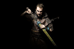 Viking warrior with sword over black background going to war Royalty Free Stock Photos