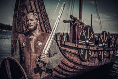 Viking warrior with sword and shield standing near Drakkar on seashore. Royalty Free Stock Photo