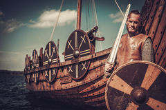 Viking warrior with sword and shield standing near Drakkar on the seashore. Royalty Free Stock Image