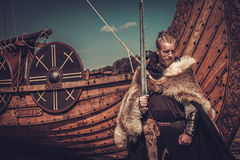 Viking warrior with sword and shield standing near Drakkar on the seashore. Stock Photos
