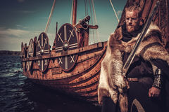 Viking warrior with sword and shield standing near Drakkar on the seashore. Serious viking warrior with sword and shield standing near Drakkar on the seashore stock photos