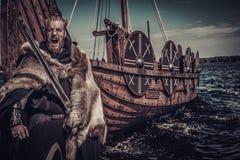 Viking warrior with sword standing near Drakkar on seashore Royalty Free Stock Photos