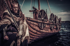 Viking warrior with sword standing near Drakkar on seashore.  royalty free stock images