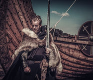 Viking warrior with sword standing near Drakkar on seashore.  stock image