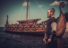 Viking warrior with sword standing near Drakkar on the seashore. Serious viking warrior with sword standing near Drakkar on the seashore royalty free stock photography