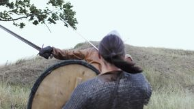 A Viking warrior throws a spear during an attack. Warriors of Vikings are Fighting during Attack. Vikings are fighting in the meadow. Medieval Reenactment stock video footage