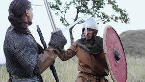 A Viking warrior throws a spear during an attack. Warriors of Vikings are Fighting during Attack. Vikings are fighting in the meadow. Medieval Reenactment stock footage