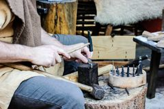Viking week in York, 2019. Man is making metal bracelet using little hummer stock image