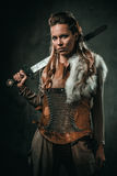Viking woman with cold weapon in a traditional warrior clothes.  stock photos