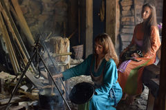 Viking woman prepares food in the pot on the fire Stock Photography