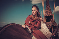 Viking woman with shield on Drakkar. Royalty Free Stock Images