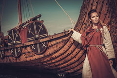 Viking woman standing near Drakkar on the seashore. Beautiful viking woman standing near Drakkar on the seashore royalty free stock images