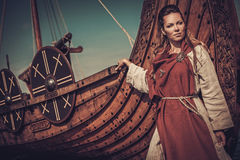 Viking woman standing near Drakkar on the seashore. Royalty Free Stock Images