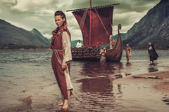 Viking woman standing near Drakkar on seashore Stock Image