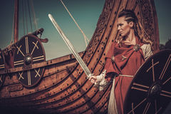Viking woman with sword and shield standing near Drakkar on the seashore. Royalty Free Stock Images