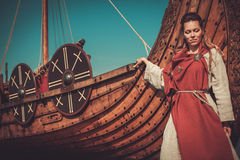 Viking woman in traditional clothes near drakkar Stock Images