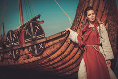Viking woman in traditional clothes near drakkar Stock Photography