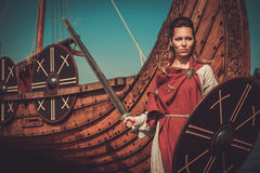 Viking woman in traditional clothes near drakkar Stock Photos