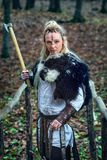 Viking woman warrior fur collar and specific makeup rising ax above head, ready to attack. Portrait of dangerous, beautiful scandinavian viking woman warrior fur royalty free stock images