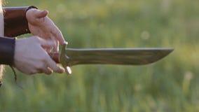 Vikingkrigaren kastar en kniv från handen för att räcka på bakgrunden av en stunningly härlig solnedgång i fältet Mycket kallt oc stock video