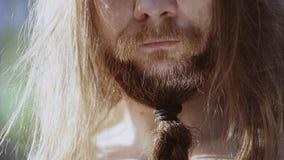 Vikingkrigaren står i skogen och blickarna in i reflexionen i hans stora kniv Medelskott från sidan och upp av framsidan lager videofilmer