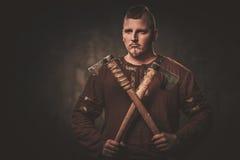 Vikingo serio con las hachas en un guerrero tradicional viste, presentando en un fondo oscuro imágenes de archivo libres de regalías