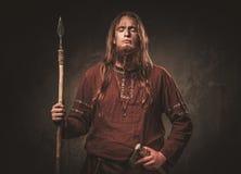 Vikingo serio con una lanza en un guerrero tradicional viste, presentando en un fondo oscuro fotografía de archivo